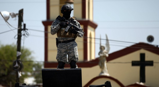 A soldier stands guard after a blockade set by members of the Santa Rosa de Lima Cartel to repel security forces during an anti-fuel theft operation.