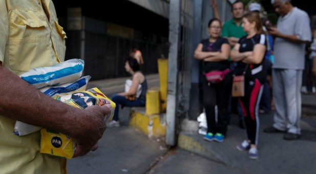 A man carrying packages of corn flour and sugar walks out from a supermarket during a blackout in Caracas, Venezuela.