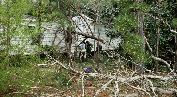 Lee County Sheriff's Deputies knock on the door of a building in order to conduct a welfare check after two back-to-back tornadoes touched down killing at least 23 people, in Beauregard, Alabama.