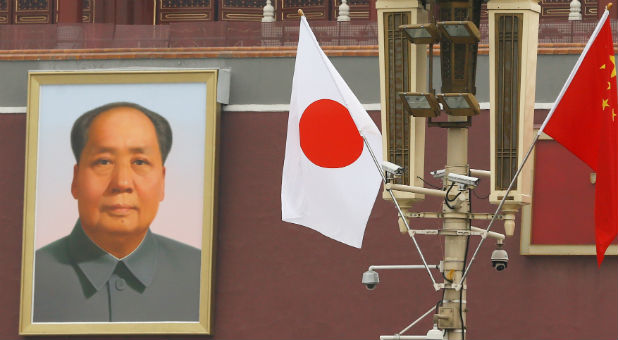 Chinese and Japanese flags flutter in front of a portrait of former Chinese chairman Mao Zedong at the Tiananmen Gate.