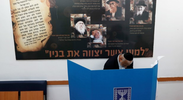 An ultra-Orthodox Jewish stands behind a voting booth as Israelis vote in a parliamentary election, at a polling station in Jerusalem.