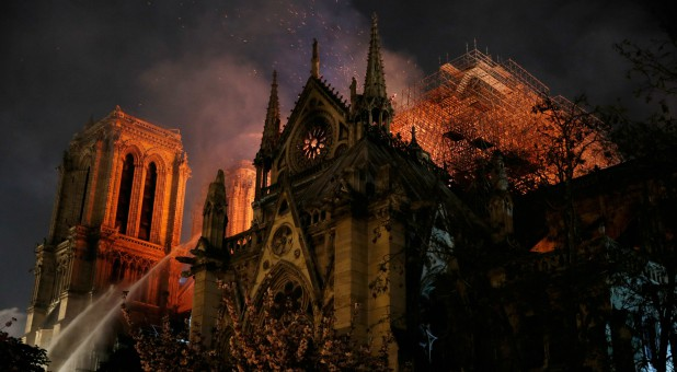 Sparks fill the air as Paris Fire brigade members spray water to extinguish flames as the Notre Dame Cathedral burns in Paris, France.
