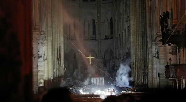 Smoke rises around the altar in front of the cross inside the Notre Dame Cathedral as a fire continues to burn in Paris, France.