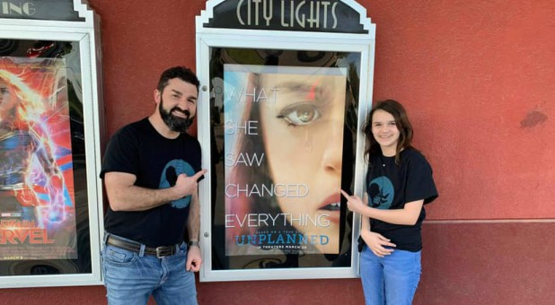 "Doug and Grace Johnson stand by a poster for ""Unplanned."""