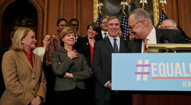 U.S. Senate Democratic leader Chuck Schumer, right, credits U.S. Senator Tammy Baldwin, D-Wis., left, for an LGBTQ cheer as they gather to announce the introduction of the Equality Act.
