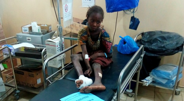 An injured girl sits inside a hospital after a suspected Boko Haram attack on the edge of Maiduguri's inner city, Nigeria.