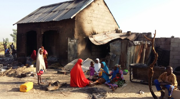 People sit near a burnt house after an attack by suspected members of the Islamist Boko Haram insurgency in Bulabulin village, Nigeria.