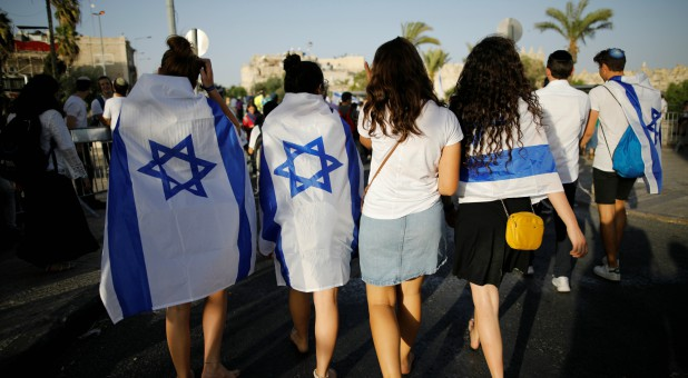 "Jewish youth covered with Israeli flags as they participate in a march marking ""Jerusalem Day"", near Damascus Gate."