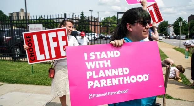 Pro-choice and pro-life protesters stand outside of Planned Parenthood.