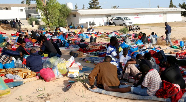 Migrants are seen with their belongings at the yard of a detention center for mainly African migrants, hit by an airstrike, in the Tajoura suburb of Tripoli, Libya.
