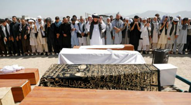 Afghan men offer funeral prayers over the coffins of the victims of a blast in a wedding in Kabul.