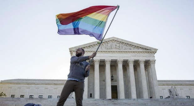 A man waves a gay flag over the Supreme Court, which is set to decide the legality of same-sex marriage on June 25.
