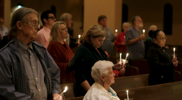 People gather at a United Methodist Church for a prayer vigil for the victims of the San Bernardino shooting. As terrorist attacks against Christians increase, some churches are taking precautions.