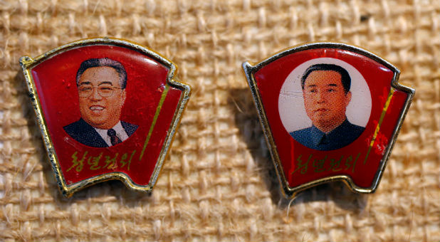 Two pins featuring former North Korean leader Kim Il Sung wearing different facial expressions.