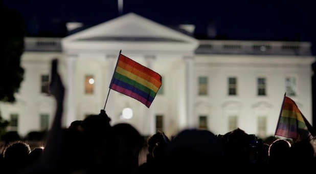 A rainbow flag is held up during a vigil.