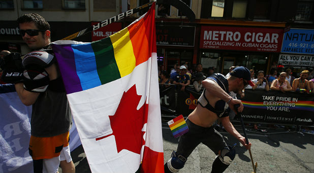 "A man holds a rainbow coloured Canadian flag attached to a hockey stick during the"" WorldPride"" gay pride Parade in Toronto."