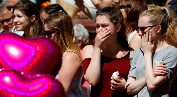People look at tributes to the victims of the attack on the Manchester Arena, in central Manchester