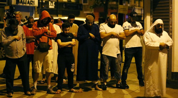 Men pray after a vehicle collided with pedestrians near a mosque in the Finsbury Park neighborhood of North London.