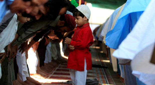 A boy stands among people offering last Friday prayers during the holy month of Ramadan in Rawalpindi, Pakistan.