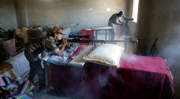 A female Kurdish fighter from the People's Protection Units (YPG) fires a long-range sniper rifle at Islamic State militants in Raqqa, Syria.