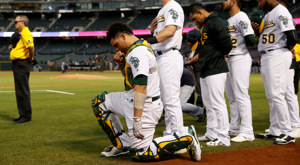 Bruce Maxwell of the Oakland Athletics kneels during the singing of the National Anthem.